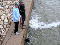 Fisheries researchers, Nathan Reynoldson and Leo Cameron, trial the sonar camera at Lock 8 on the Murray River.