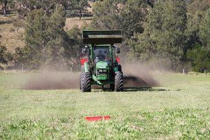 A tractor in a paddock spreading fertiliser