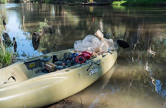 Paddle boat on the bank of the Lachlan River (NSW Central West) filled with seized fishing lines and cast nets