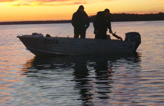 Fishermen in boat at dawn, Photo: Britt Anderson