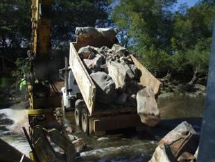 A truck dumping large rocks.