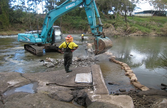 Excavator removing concrete from waterway