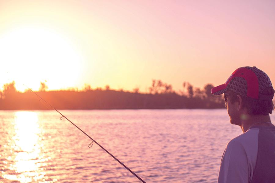 A man fishing at dusk