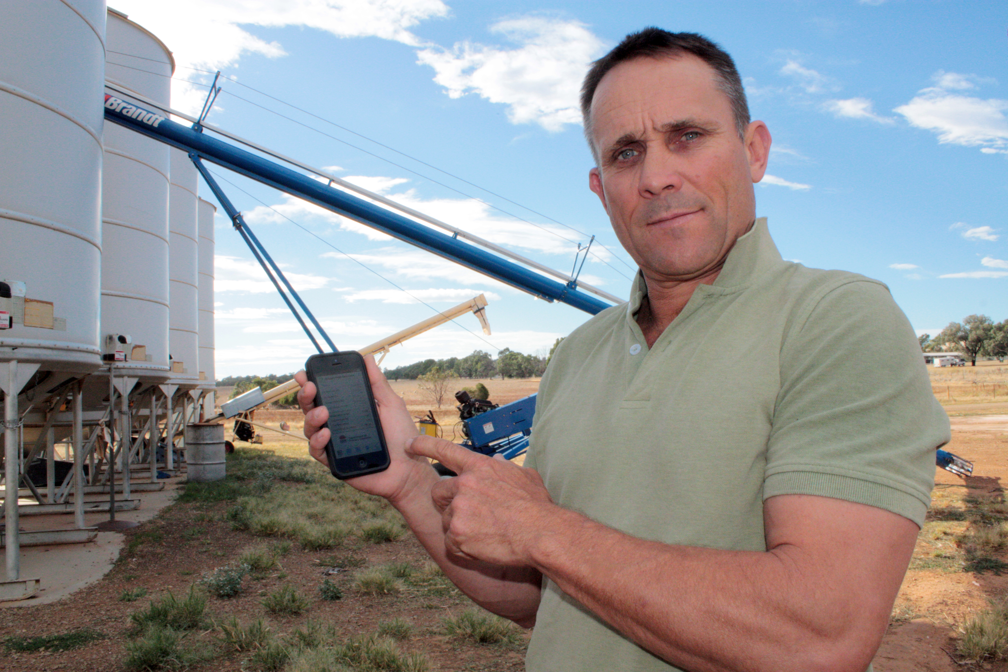 Geoff  Casburn with mobile phone showing the Drought Feed Calculator app