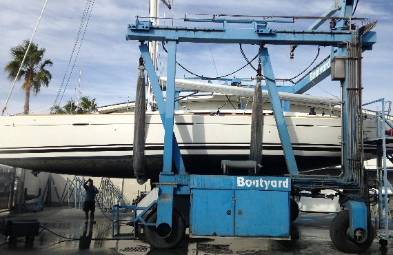 Boat on hoist being cleaned at boatyard