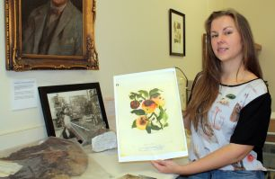 Dr Jordan Bailey holding artwork from NSW DPI's Biosecurity Collections
