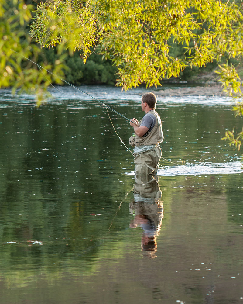 A man stands waiting for a bite in a flowing waterway with his trout fishing rod