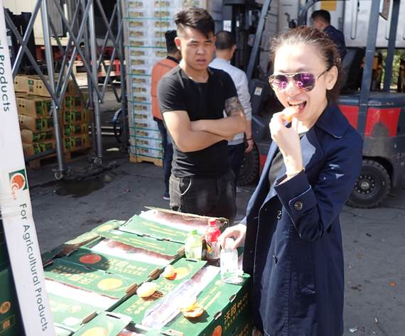 A lady tasting fruit at wholesale markets in China