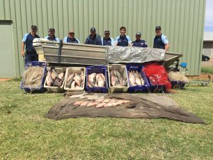 Fisheries Officers stand behind confiscated equipment and retrieved fish.