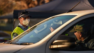 A policeman wearing a mask checking a drivers details