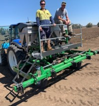 two people standing on variable rate applicator attached to back of tractor