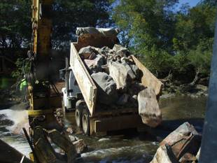 A truck dumping large rocks.