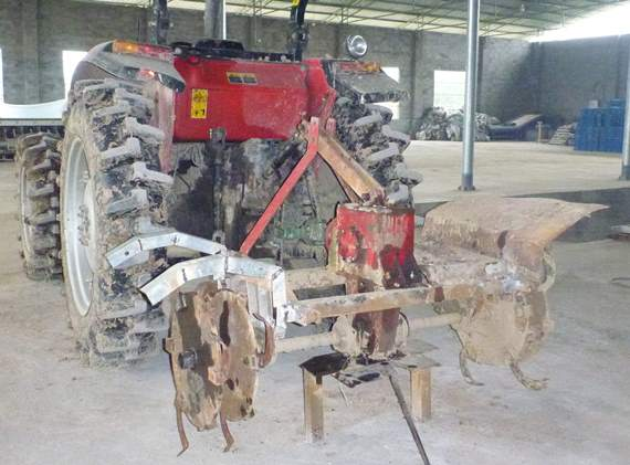 A tractor with a rotary hoe implement